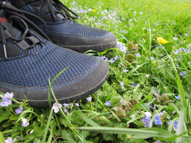Barfußschuhe von Sole Runner auf einer Frühlingswiese mit Blumen